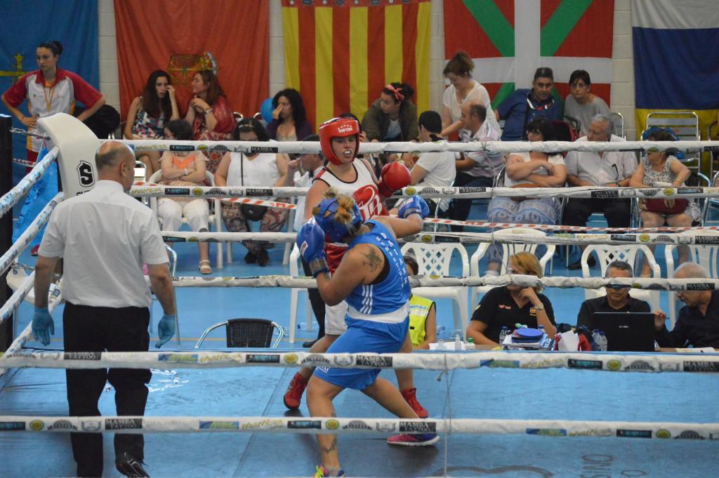 Sobre el cuadrilátero del Polideportivo de Novo Mesoiro dos competidoras gallegas, pujan deportivamente por la Plata y el Oro en la final del peso máximo femenino. Al fondo y de izquierda a derecha