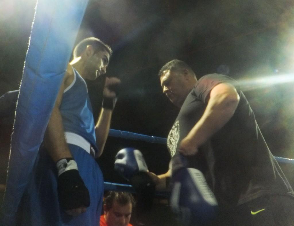 El ritual de competición se inicia con el maestro Luis Torrado enguantando y aleccionando al joven alumno Neo. boxeodemedianoche Blanco